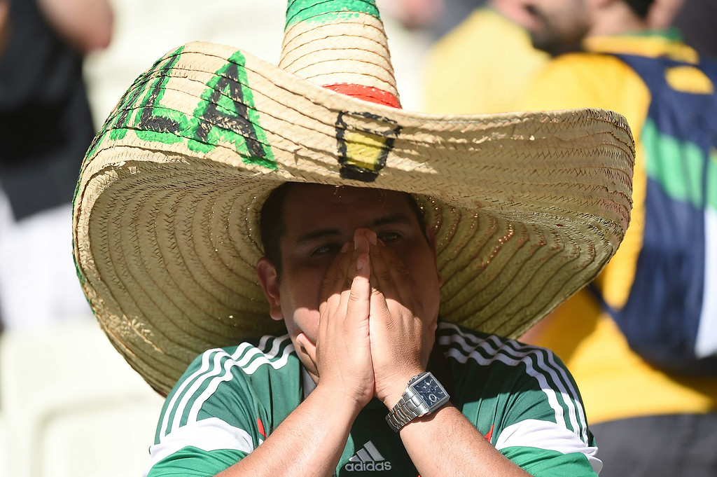 . A Mexican supporter reacts after their team\'s defeat in the Round of 16 football match between Netherlands and Mexico at Castelao Stadium in Fortaleza during the 2014 FIFA World Cup on June 29, 2014. AFP PHOTO / EMMANUEL DUNAND