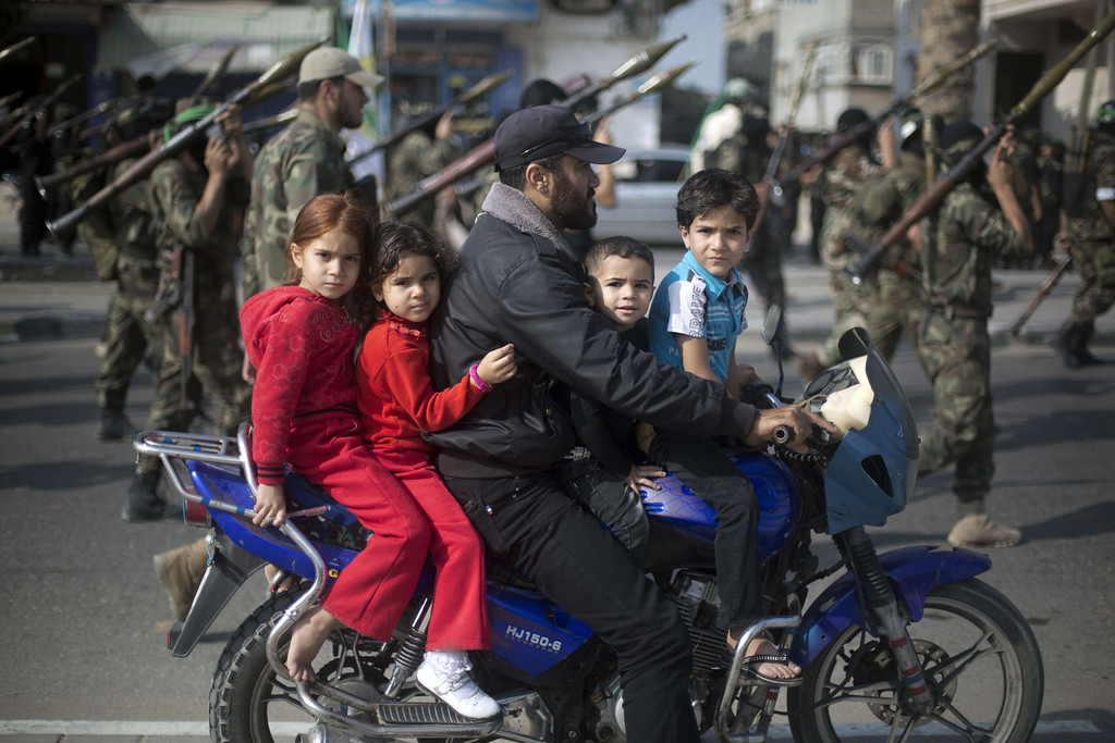 ". A Palestinian man rides a motorcycle with his children past masked militants of Ezzedine al-Qassam Brigades, Hamas\'s armed wing, as they parade in Jabalia refugee camp, northern Gaza Strip, on November 14, 2013, during an anti-Israel march as part of the celebrations marking the first anniversary of what Israel named the ""Pillar of Defense\"" Operation. AFP PHOTO/MOHAMMED ABED/AFP/Getty Images"