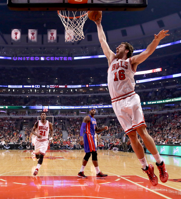 . Chicago Bulls forward Pau Gasol goes in for the dunk as Jimmy Butler (21) and Andre Drummond (0) watch during the first half of an NBA basketball game against the Detroit Pistons Monday, Nov. 10, 2014, in Chicago. (AP Photo/Charles Rex Arbogast)