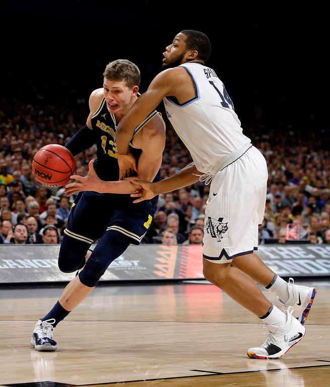 . Michigan\'s Moritz Wagner (13) drives around Villanova\'s Omari Spellman (14) during the first half in the championship game of the Final Four NCAA college basketball tournament, Monday, April 2, 2018, in San Antonio. (AP Photo/David J. Phillip)