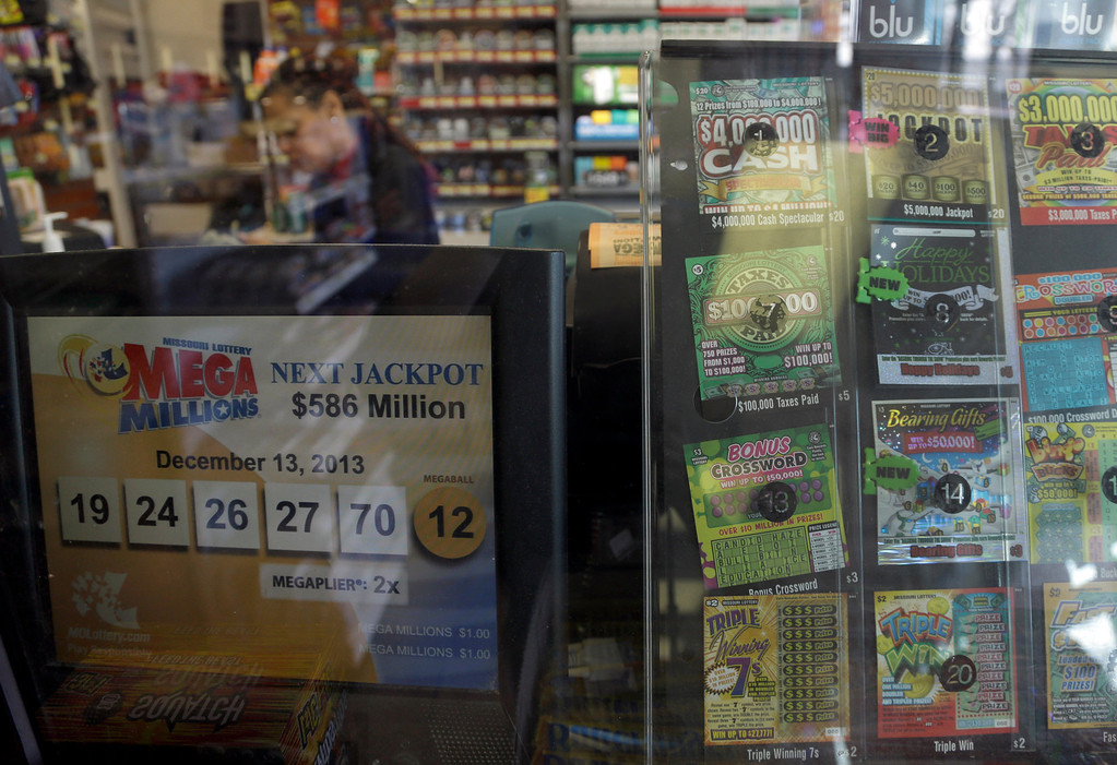 . Anita Watson works behind a counter at Energy Express convenience store selling Mega Millions lottery tickets Monday, Dec. 16, 2013, in St. Louis. The Mega Millions jackpot now stands at an estimated $586 million with the next drawing set for Tuesday night. (AP Photo/Jeff Roberson)