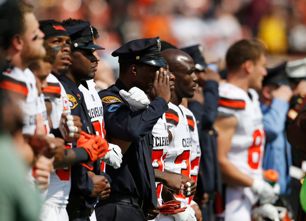 . Cleveland Browns players and Cleveland police stand together during the national anthem before an NFL football game between the Pittsburgh Steelers and the Cleveland Browns, Sunday, Sept. 10, 2017, in Cleveland. (AP Photo/Ron Schwane)