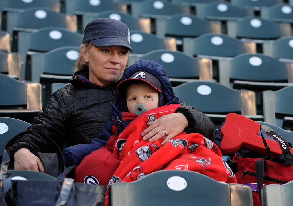. DENVER, CO. - APRIL 23:  Virginia Minick huddled with her 18-month old son Henry at Coors Field Tuesday. The temperature never rose above freezing during the game. The Atlanta Braves defeated the Colorado Rockies 4-3 at Coors Field Tuesday, April 23, 2013.  The first game of the doubleheader Tuesday was a make-up from Monday night\'s postponement due to weather.  Photo By Karl Gehring/The Denver Post