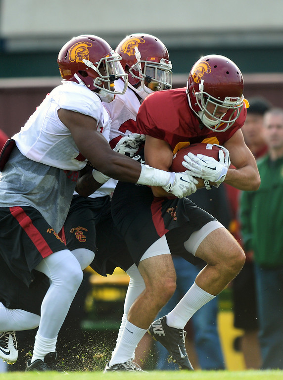 . USC LB Quinton Powell, left, and DB Chris Hawkins stop WR George Katrib during practice, Tuesday, March 25, 2014, at USC. (Photo by Michael Owen Baker/L.A. Daily News)