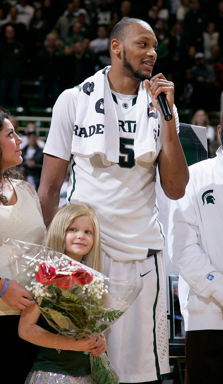 ". FILE - In this March 6, 2014 file photo, Michigan State senior Adreian Payne addresses the crowd during a senior day ceremony as he stands with his guest, Lacey Holsworth, who is battling cancer, following an NCAA college basketball game against Iowa, in East Lansing, Mich. The father of  8-year-old Lacey Holsworth, who befriended Michigan State basketball star Adreian Payne says his daughter has died. Matt Holsworth says Lacey Holsworth died at their St. Johns, Mich., home late Tuesday, April 8, 2014 ""with her mommy and daddy holding her in their arms.\"". (AP Photo/Al Goldis)"