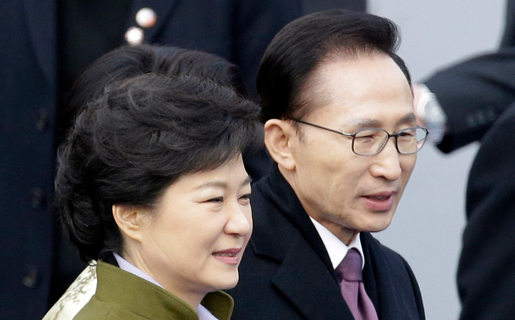 . South Korea\'s new President Park Geun-hye, left, walks with outgoing President Lee Myung-bak after her inauguration ceremony as the 18th South Korean president at the National Assembly in Seoul, South Korea, Monday, Feb. 25, 2013. Seen on her cheek is a four-inch gash she suffered in the 2006 knife attack by a convicted criminal who slashed her face while she was shaking hands with voters. (AP Photo/Lee Jin-man)