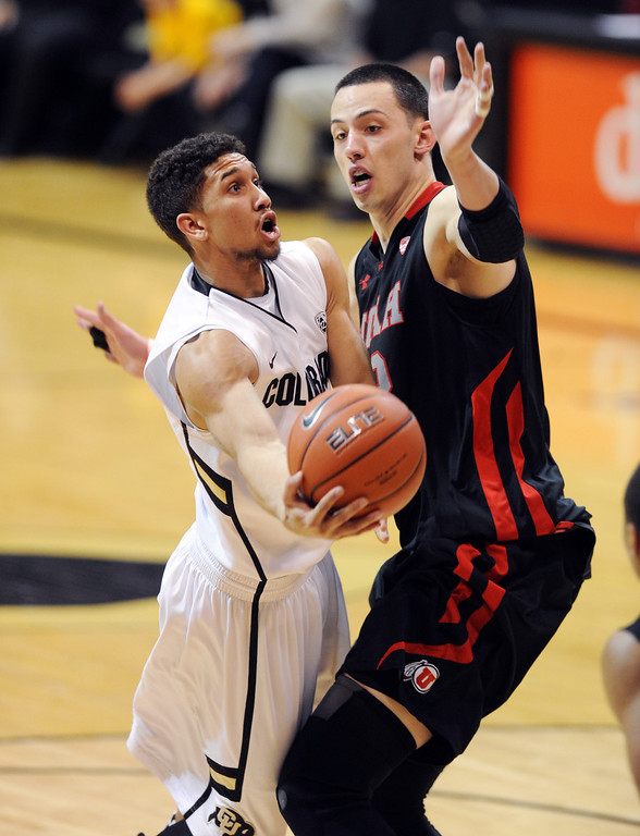 . Askia Booker of CU shoots around Jason Washburn of Utah during the second half of the February 21st, 2013 game in Boulder. For more photos of the game, go to www.dailycamera.com. Cliff Grassmick / February 21, 2013