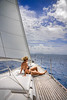 Attractive woman sitting on the front of large and luxurious sailboat sailing through the tropics.