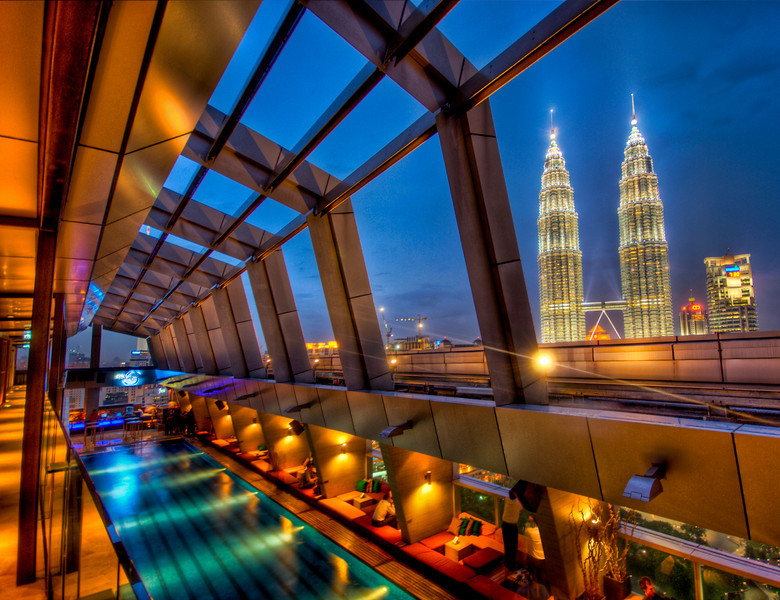 The Sky Bar in Kuala Lumpur with a View of Petronas This bar is up on top of the roof and it is all open air. There is a pool down there that is always available for use, and it is surrounded by a ultra-chic bar. It was raining when I took this… I am up on the 2nd level of the bar, where there is a spa… you can see the little massage rooms down the lefthand side there.- Trey RatcliffClick here to read the rest of this post at the Stuck in Customs blog.
