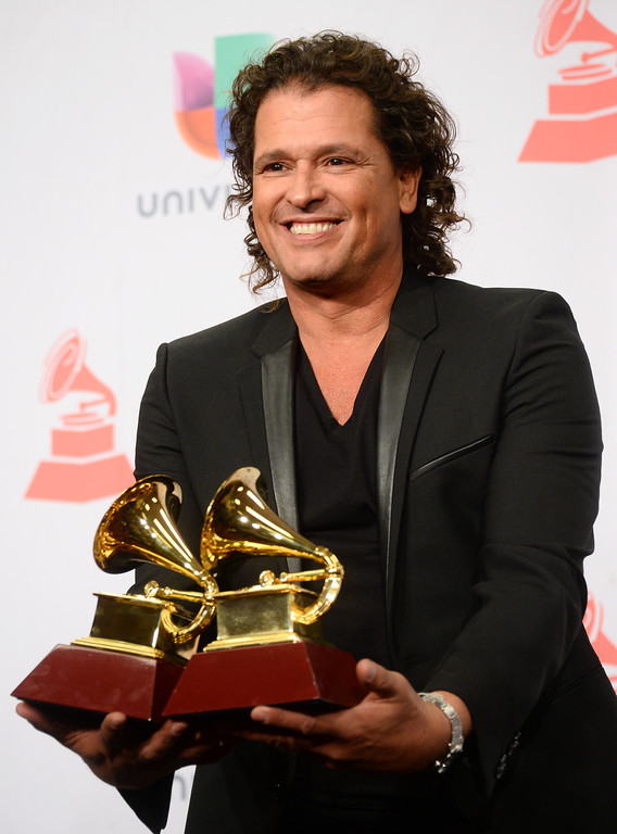 """. Carlos Vives poses in the press room with the awards for best contemporary tropical album for \""""Mas + Corazon Profundo\"""" and best tropical song for \""""Cuando Nos Volvamos A Encontrar\"""" at the 15th annual Latin Grammy Awards at the MGM Grand Garden Arena on Thursday, Nov. 20, 2014, in Las Vegas. (Photo by Al Powers/Invision/AP)"""