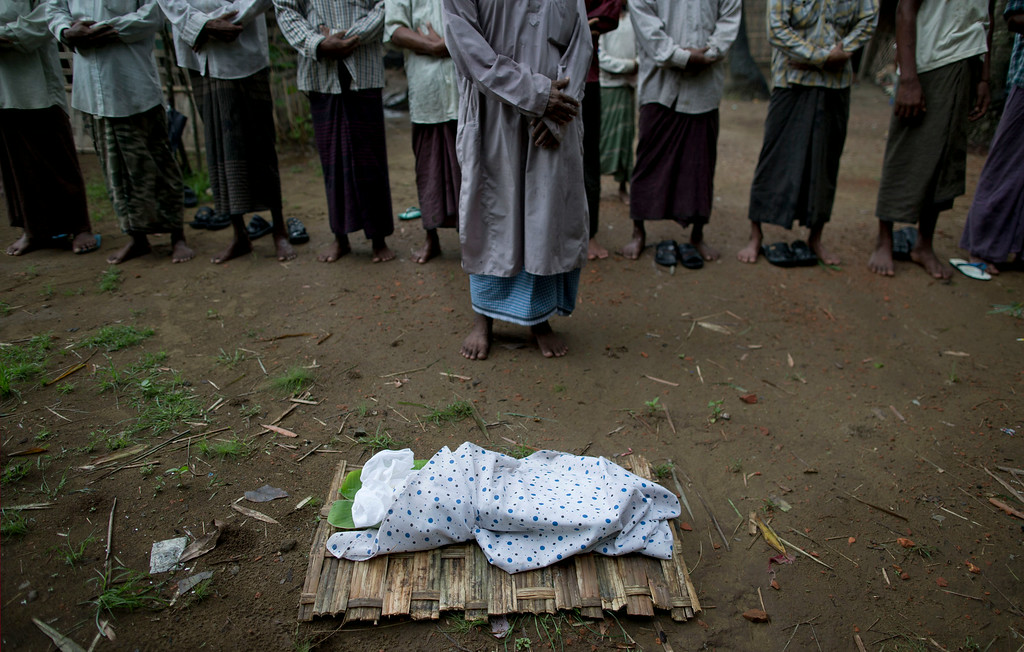 . In this June 27, 2014 photo, men stand before the corpse of Shamshu Nahad\'s daughter in prayer at a back yard of a mosque in Dar Paing village, north of Sittwe, Rakhine state, Myanmar. Cloaked in a white clothe, the little body is placed on a bamboo mat ahead of her burial. With little or no access to life-saving medical care, the number of people dying is steadily increasing. Pregnant mothers and their newborns are among the most vulnerable. (AP Photo/Gemunu Amarasinghe)
