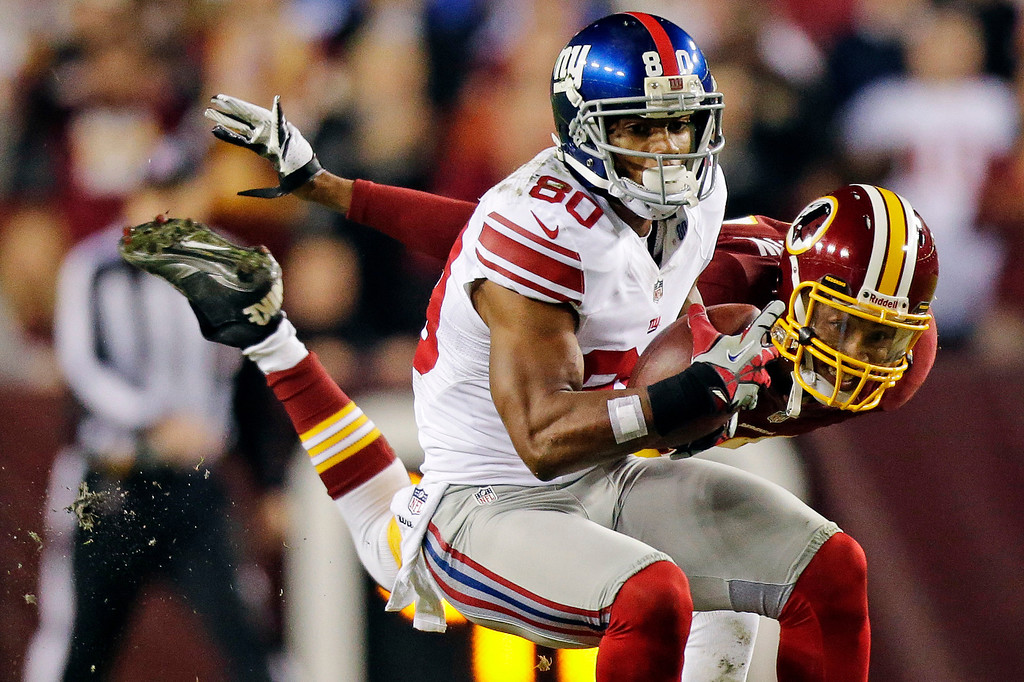 . New York Giants wide receiver Victor Cruz (80) pulls in a pass under pressure from Washington Redskins defensive back Cedric Griffin during the first half of an NFL football game in Landover, Md., Monday, Dec. 3, 2012. (AP Photo/Evan Vucci)