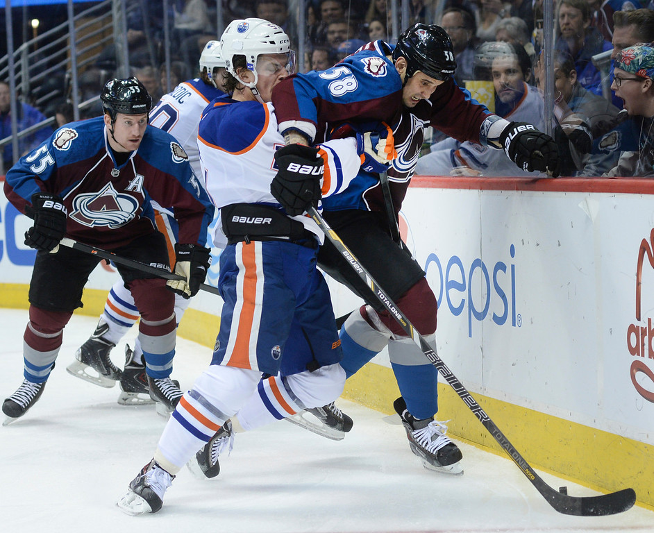 . DENVER, CO. - DECEMBER 19: Edmonton center Anton Lander (51) and Colorado wing Patrick Bordeleau (58) battled for the puck in the first period. The Colorado Avalanche hosted the Edmonton Oilers in an NHL game at the Pepsi Center Thursday night, December 19, 2013.  Photo By Karl Gehring/The Denver Post