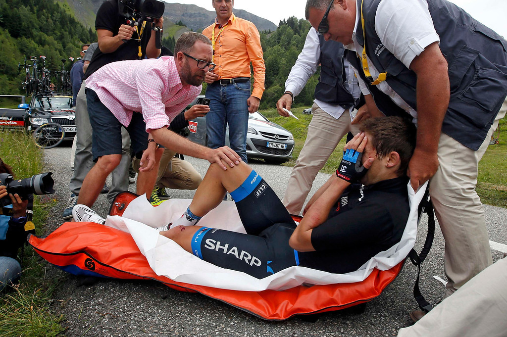 . Garmin-Sharp team rider Jack Bauer of New Zealand receives medical care after crashing during the 204.5 km stage of the centenary Tour de France cycling race from Bourg d\'Oisans to Le Grand Bornand, in the French Alps, July 19, 2013.  REUTERS/Eric Gaillard