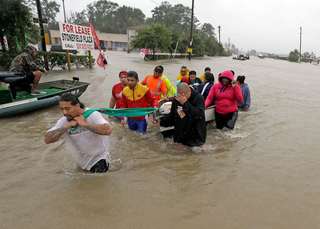 . Evacuees wade down Tidwell Road as floodwaters from Tropical Storm Harvey rise Monday, Aug. 28, 2017, in Houston. (AP Photo/David J. Phillip)