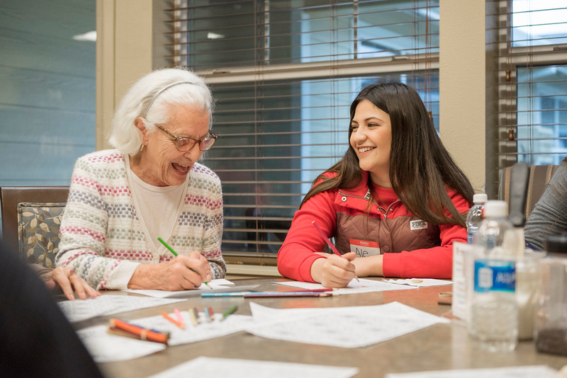 """Elizabeth """"Beth"""" Dionisio (left) colors with Ale Becerra, 20 (right) as part of the RHA training and student leadership program for residential life where student volunteers and advisors talk, bake cookies, and color with elderly at Amber Grove Retirement on Friday, January 20, 2017 in Chico, Calif. (Jason Halley/University Photographer)"""
