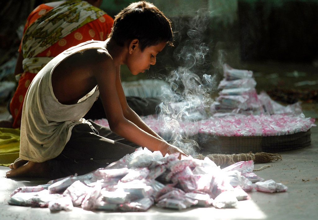 """. A child packs up cigarettes in a small bidi (cigarette) factory at Haragach in Rangpur district, Bangladesh July 13, 2013. According to a 2012 study by US-based NGO, Campaign for Tobacco-Free Kids, over 45,000 people in Bangladesh are employed in manufacturing inexpensive cigarettes known as bidis and this number includes \""""many women and children working in household based establishments where they make low wages and live in poverty.\"""" A 2011 research paper about bidi workers in Bangladesh, published in the journal Tobacco Control, says that working conditions can involve poor ventilation and exposure to tobacco dust, which can cause a range of health problems including respiratory and skin diseases. International attention has been focused on workers\' safety in Bangladesh since the disaster at Rana Plaza, a garment factory complex which collapsed in April, killing 1,132 workers.  REUTERS/Andrew Biraj"""