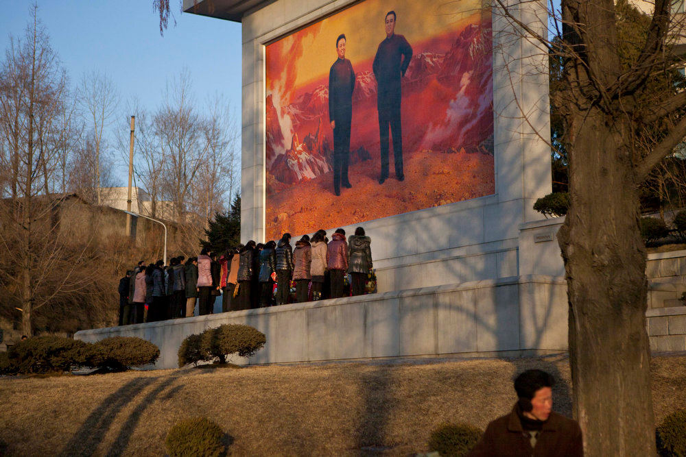 . North Koreans stand before a roadside mosaic of the late leaders Kim Il Sung and Kim Jong Il to pay their respects on Friday, Feb. 15, 2013. (AP Photo/David Guttenfelder)