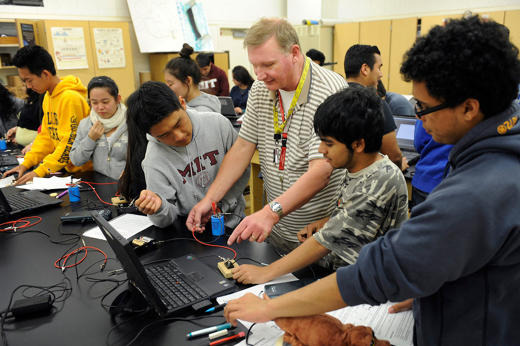 . Poly High School physics teacher Jim Schwagle helps students a capacitor experiment, Wednesday, March 20, 2013. Poly High School will become a pilot school in the Fall when it becomes a pilot school. Pilot schools have greater autonomy over scheduling, curriculum and budgets. (Michael Owen Baker/Staff Photographer)