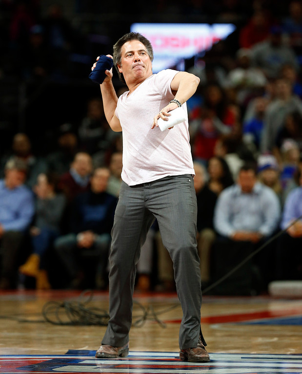. Detroit Pistons owner Tom Gores throws T-shirts to fans from the floor during a timeout against the Orlando Magic in the second half of an NBA basketball game in Auburn Hills, Mich., Wednesday, Jan. 21, 2015. (AP Photo/Paul Sancya)