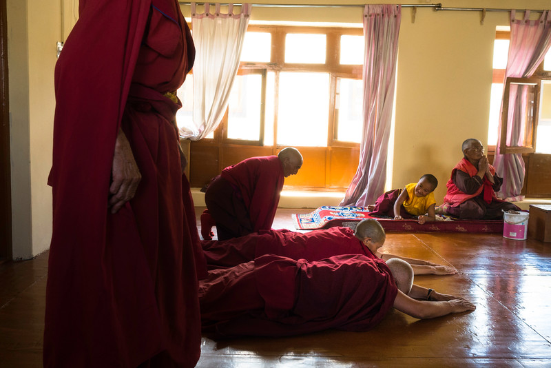 Skarma plays around as the other nuns perform traditional Buddhist prostrations. She tries her best to follow all the rituals and imitate the elderly nuns.