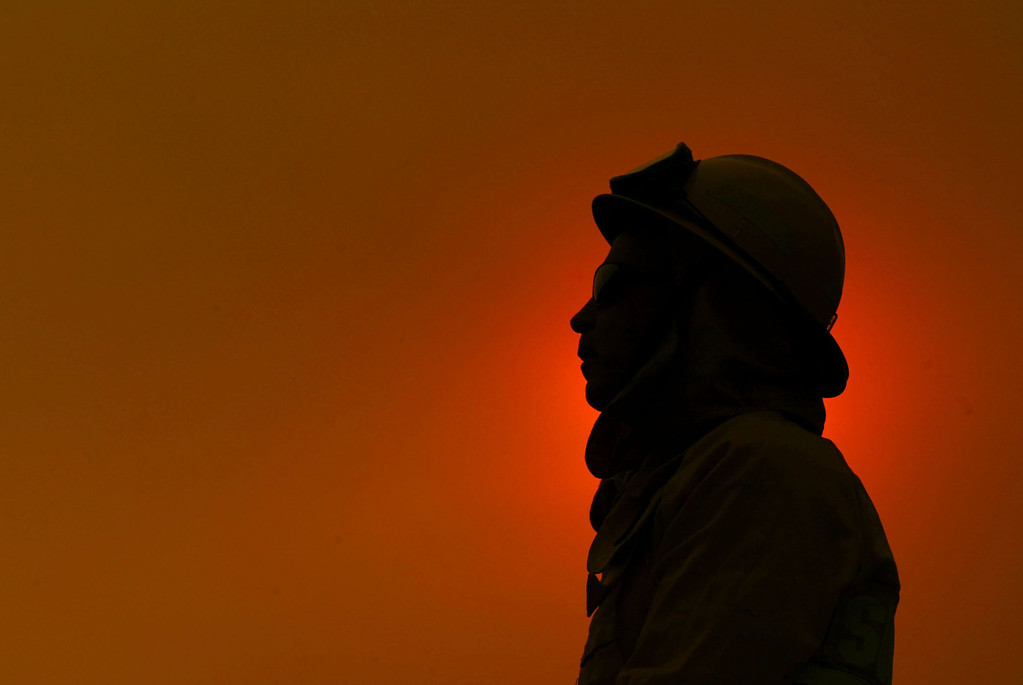 . SAN DIEGO - OCTOBER 27:  An exhausted firefighter from Marin County Fire Department is silhouetted against the smoke-shrouded sun near near the Cedar Fire October 27, 2003 near Lakeside in San Diego, California. The death toll stands at 13, with more than 1,000 homes being reduced to ashes as southern California fires continue to burn. Winds have eased a bit, but 30,000 homes remain threatened by the fires, which have charred more than 400,000 acres, according to officials. Davis, who has activated the National Guard, predicted damages will be in the billions of dollars.  (Photo by Donald Miralle/Getty Images)