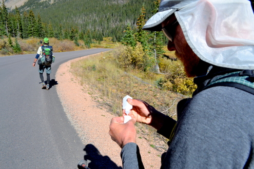 . Junaid Dawud prepares chemicals to clean water as Luke DeMuth continues down Guanella Pass Road into Georgetown. The friends have hiked 1,300 miles and climbed 57 of the state\'s 58 14,000-foot peaks and plan to finish their 70-day mission Sunday on Longs Peak.