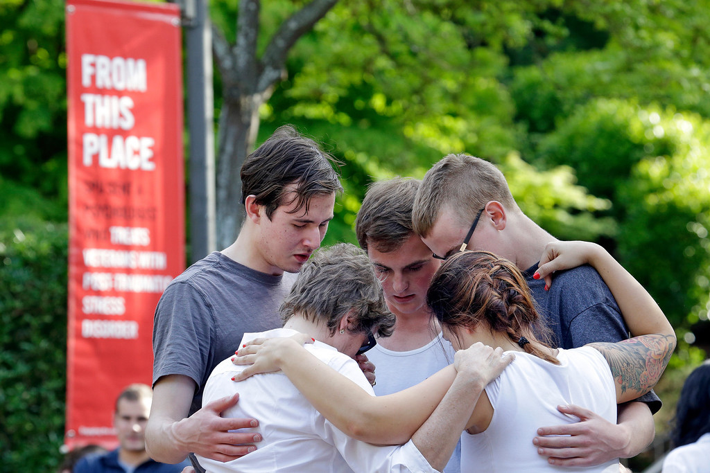 . Students and faculty pray together following a shooting on the campus of Seattle Pacific University Thursday, June 5, 2014, in Seattle. Seattle police say there are four victims in a shooting and say one suspect is in custody. Police say one man and one woman have life-threatening injuries while another man and another woman are reported in stable condition.(AP Photo/Elaine Thompson)