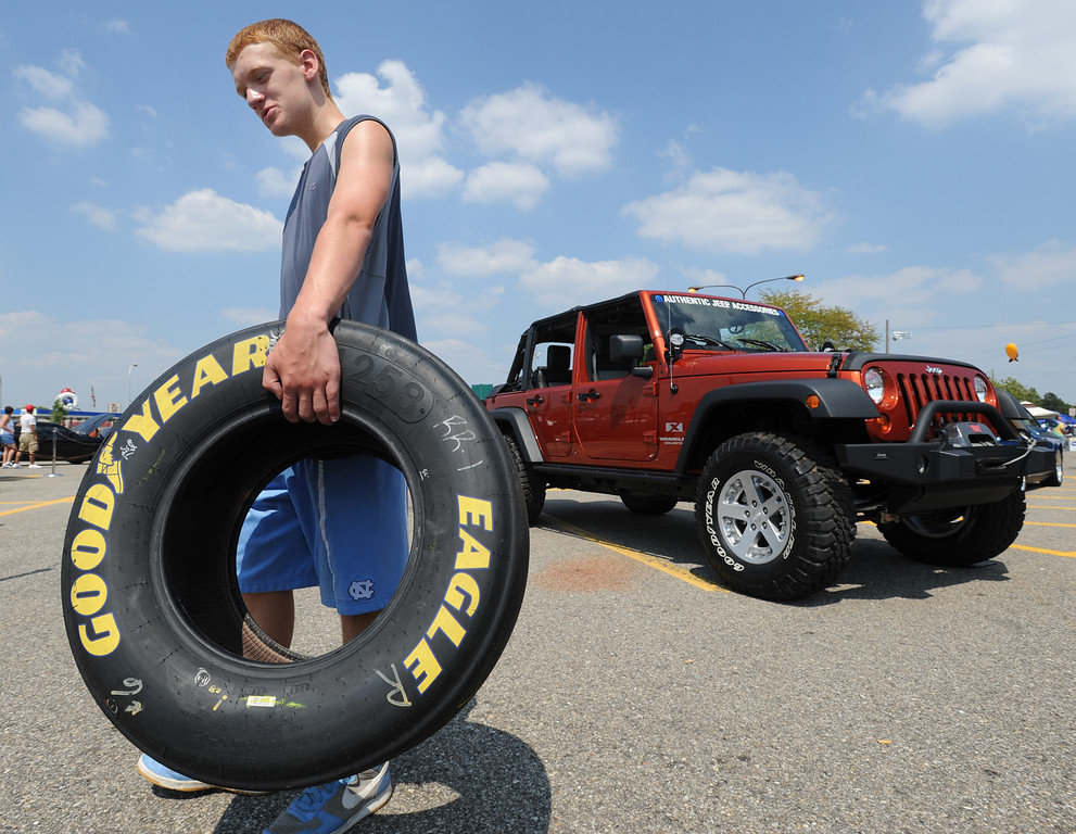 . Michael Lay, age 13, of Royal Oak, Mich., carries his contest giveaway winnings, a used car tire that was once used on a NASCAR race vehicle during one of the NASCAR races.  Lay, who is a NASCAR fan, said he will clean it up and use the tire as a decoration in his room.  His mom consented.  Photo taken during the Woodward Dream Cruise on Saturday, August 15, 2009, in Royal Oak, Mich.  (The Oakland Press/Jose Juarez)
