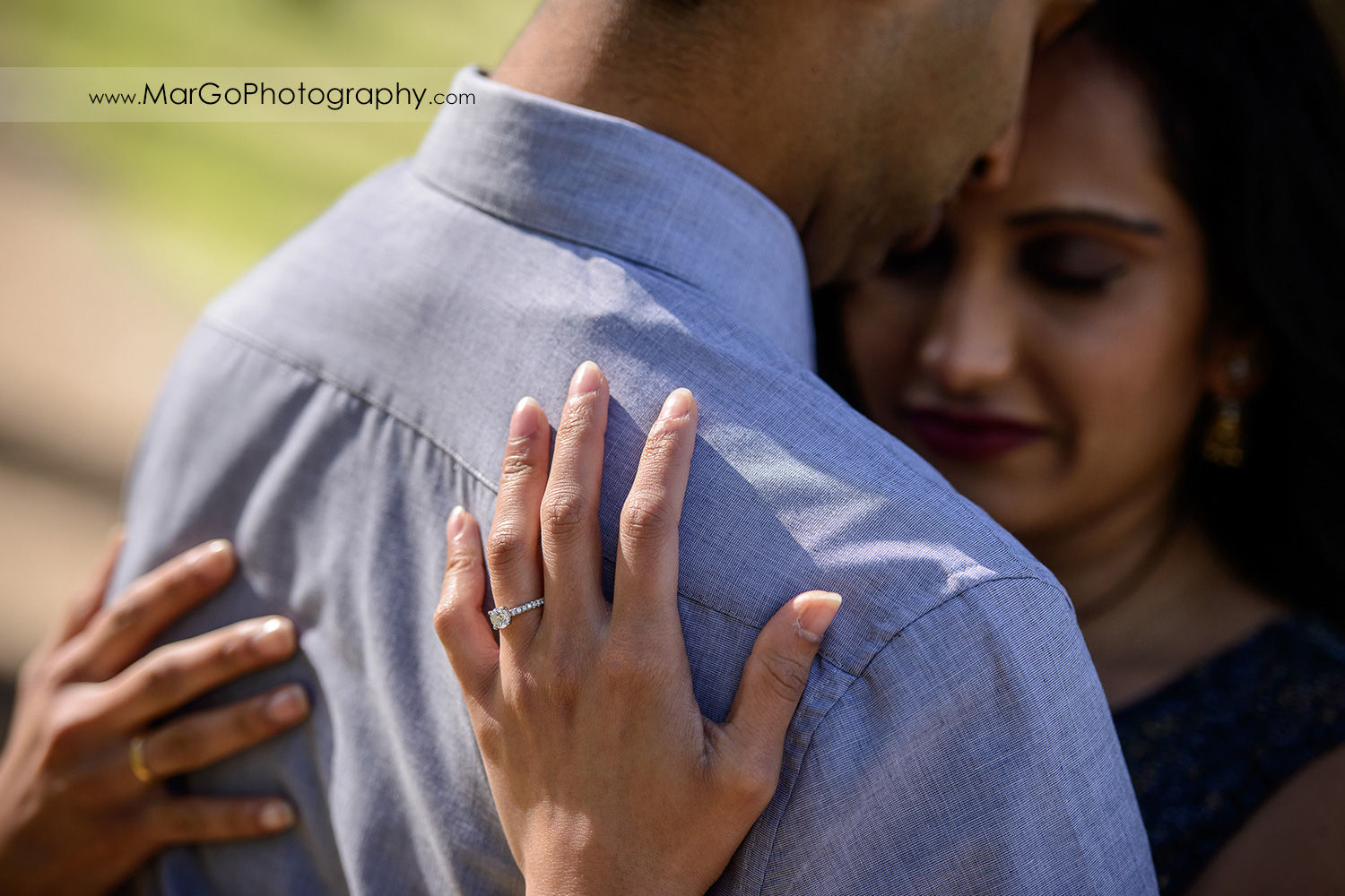 ring shot of Indian couple in blue clothes during engagement session at San Francisco Presidio Park