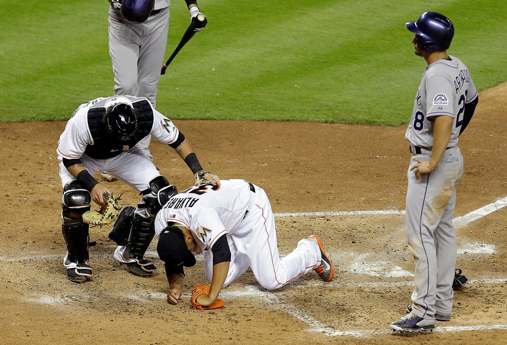 . Miami Marlins catcher Jarrod Saltalamacchia, left, checks on starting pitcher Henderson Alvarez (37) after Alvarez collided with Colorado Rockies\' Nolan Arenado, right, who scored on a wild pitch in the fourth inning of a baseball game on Wednesday, April 2, 2014, in Miami. (AP Photo/Lynne Sladky)
