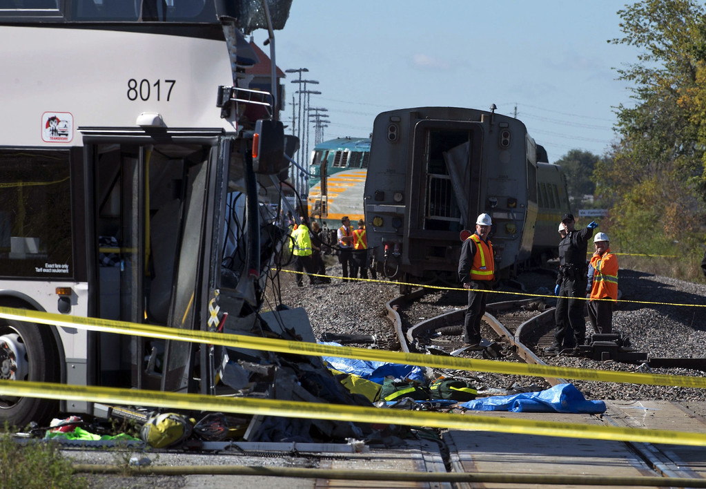 . Emergency workers look over the site of a crash between a city bus and Via Rail train, Wednesday, Sept. 18, 2013 in Ottawa, Canada. Witnesses said the bus went through a closed crossing barrier. (AP Photo/The Canadian Press, Adrian Wyld)