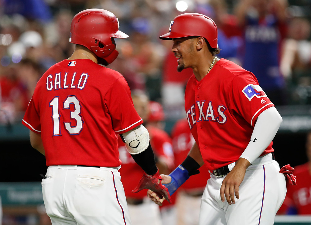. Texas Rangers\' Joey Gallo (13) celebrates his two-run home run with Ronald Guzman, right,  during the seventh inning of a baseball game against the Cleveland Indians, Friday, July 20, 2018, in Arlington, Texas. (AP Photo/Jim Cowsert)