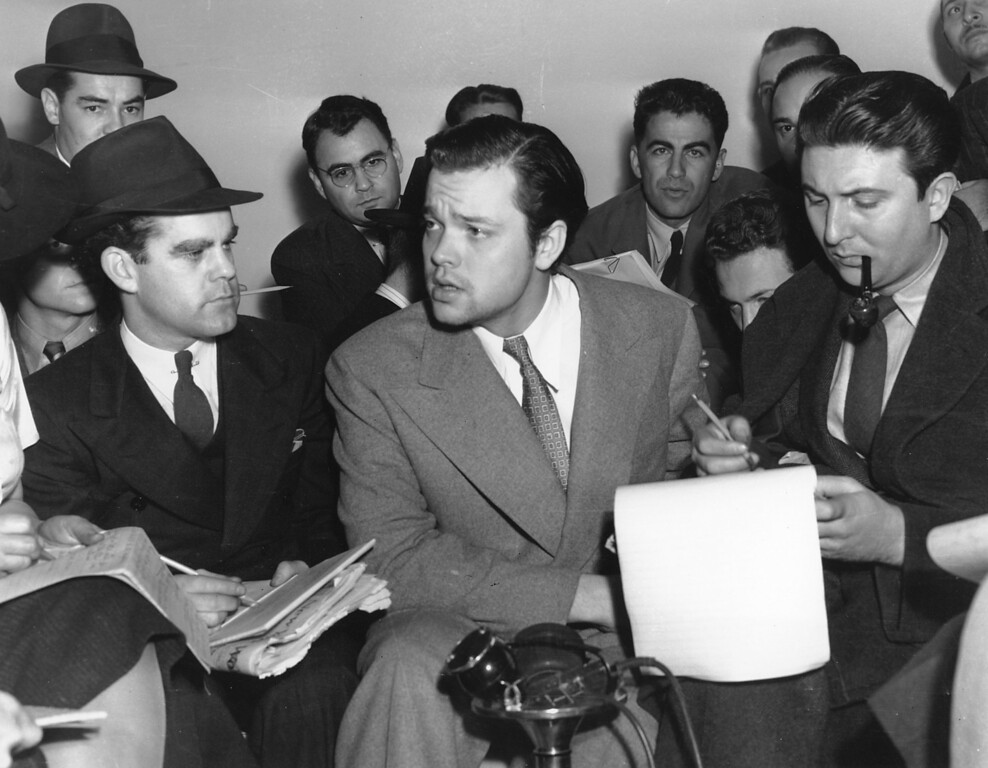 """. Orson Welles, center, explains to reporters on Oct. 31, 1938 his radio dramatization of H.G. Wells\' \""""War of the Worlds.\""""  Meanwhile, Columbia Broadcasting System made public the transcript of the dramatization, which was aired the night of Oct. 30 and caused thousands of listeners to panic because of the realistic broadcast of an imaginative invasion of men and machines from Mars.  (AP Photo)"""