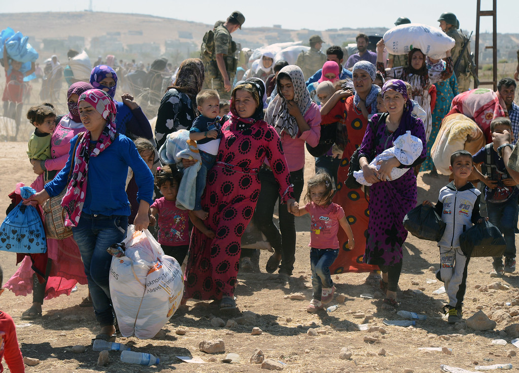 . Syrian refugee women and children gather at the border in Suruc, Turkey, Saturday, Sept. 20, 2014. TSeveral thousand Syrians, most of them Kurds, crossed into Turkey on Friday to find refuge from Islamic State militants who have barreled through dozens of Kurdish villages in northern Syria in the past 48 hours. (AP Photo)