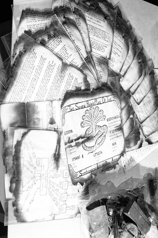 . Los Angeles police displayed these copies of Symbionese Liberation Army literature in Los Angeles, May 20, 1974 which were recovered from the burned remains of a house in which six SLA members died in a gunfight on Friday. Upper left is an organization chart titled The Symbionese War Council & Main Combat Units. (AP Photo/Jeff Robbins)