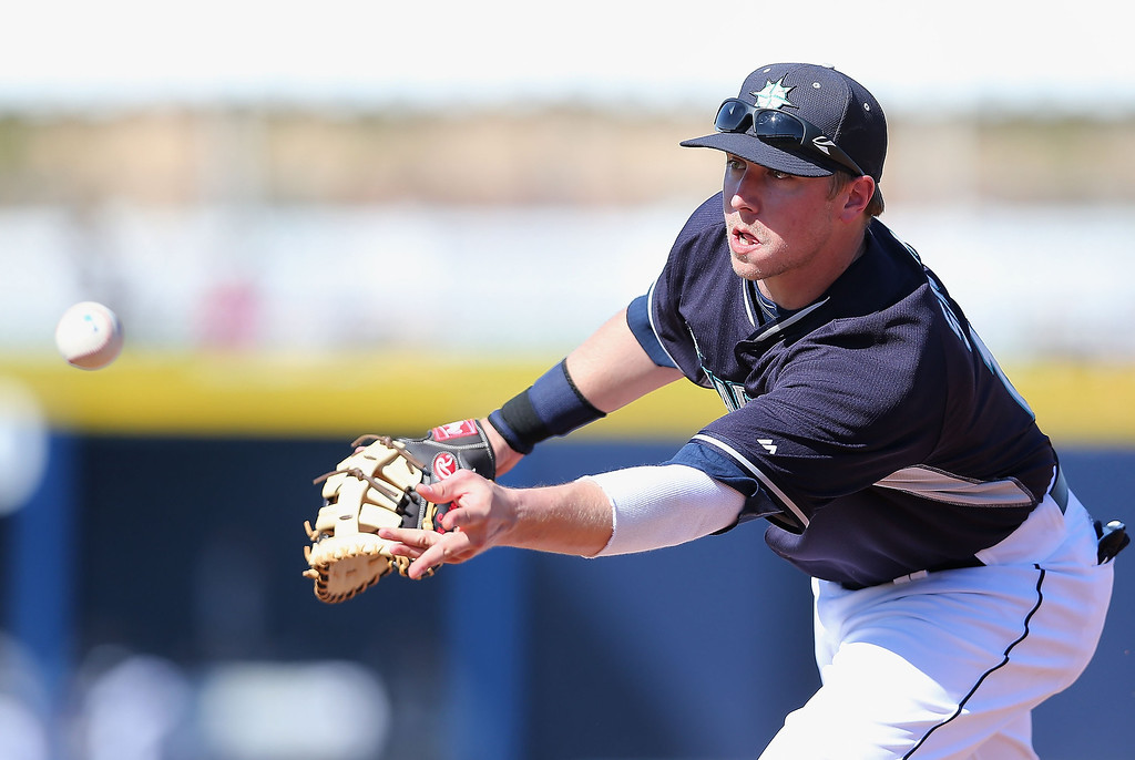 . Infielder Justin Smoak #17 of the Seattle Mariners fields a ground ball out against the Colorado Rockies during the spring training game at Peoria Stadium on March 3, 2014 in Peoria, Arizona.  (Photo by Christian Petersen/Getty Images)