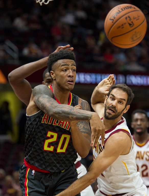 . Atlanta Hawks\' John Collins (20) passes past Cleveland Cavaliers\' Jose Calderon during the first half of an NBA pre-season basketball game in Cleveland, Wednesday, Oct. 4, 2017. (AP Photo/Phil Long)