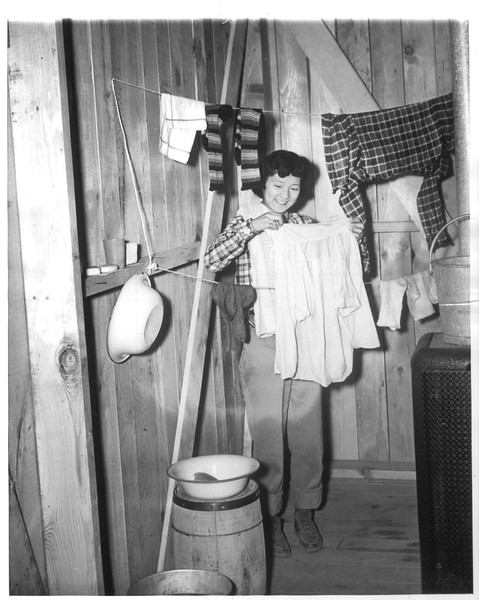 """""""Japanese At Home In Evacuation City -- Shizuko Yamada does her washing at the reception center where alien and American-born Japanese are being evacuated for the duration"""" -- caption on photograph"""
