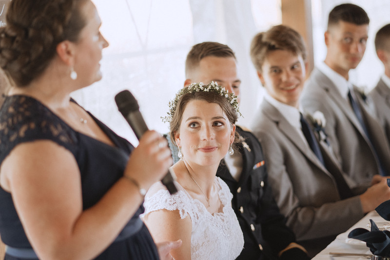 The bride smiles as her sister delivers a speech.