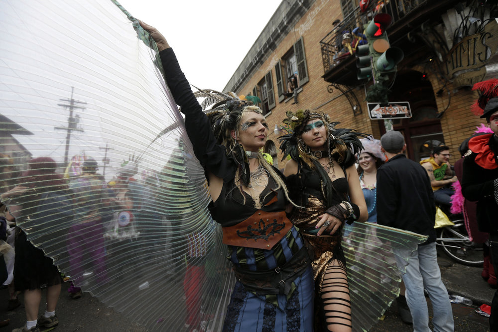 . Revelers show off their costumes as they march through the Bywater section of New Orleans during the Society of Saint Anne walking parade during Mardi Gras day, Tuesday, Feb. 12, 2013.  Despite threatening skies, the Mardi Gras party carried on as thousands of costumed revelers cheered glitzy floats with make-believe monarchs in an all-out bash before Lent.   Crowds were a little smaller than recent years, perhaps influenced by the forecast of rain. Still, parades went off as scheduled even as a fog settled over the riverfront and downtown areas.  (AP Photo/Gerald Herbert)