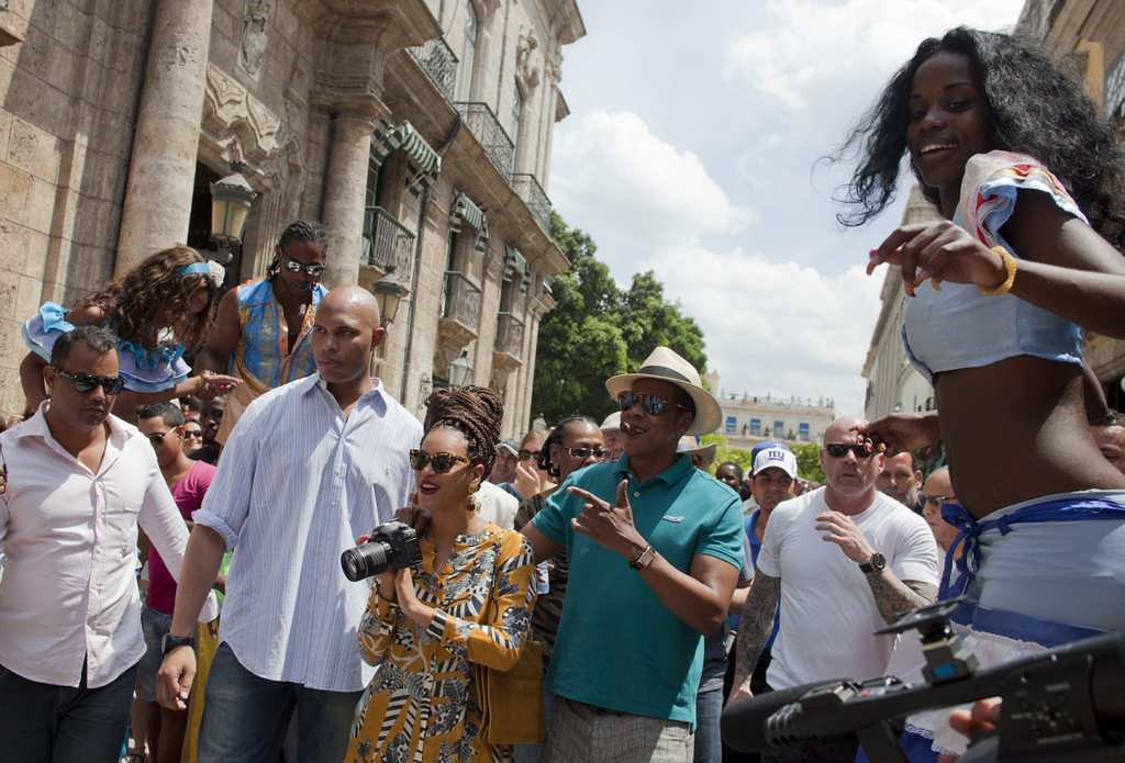 . Surrounded by body guards, Beyonce and Jay-Z continue their tour while a street performer on stilts, right, entertains them. Hey, Beyonce, take a picture of that! (Associated Press: Ramon Espinosa)