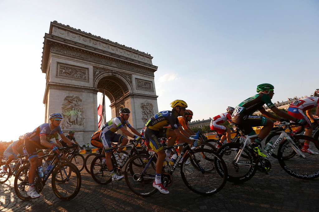 . The pack of riders cycles past the Arc de Triomphe during the 133.5km final stage of the centenary Tour de France cycling race from Versailles to Paris Champs Elysees, July 21, 2013.  REUTERS/Jean-Paul Pelissier