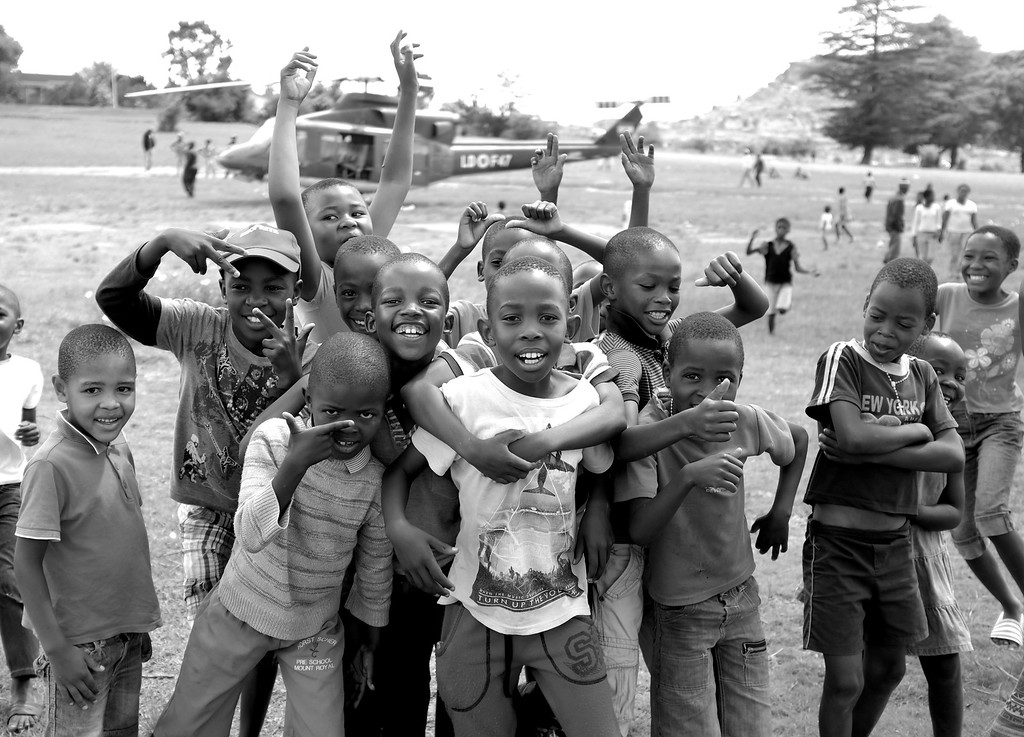 . Provided only in Black and White, this image taken by Britain\'s Prince Harry shows Lesothan children posing for the camera after Prince Harry disembarked a Lesothan Army Helicopter to visit a Mamohato Network Club help by Prince Harry\'s charity Sentebale for children living with HIV at St Paul Centre on Dec. 9, 2014, in Leribe, Lesotho.   (AP Photo / HRH Prince Henry of Wales)