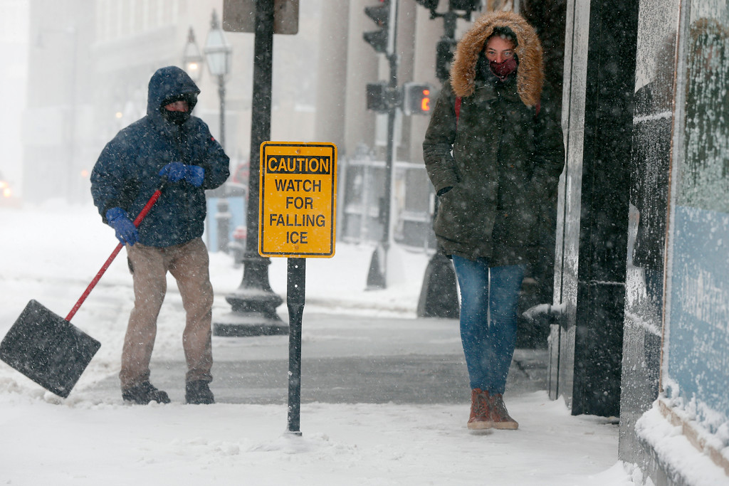 . People content with a snowstorm, Tuesday, March 13, 2018, in Boston. (AP Photo/Michael Dwyer)