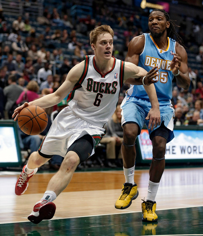 . Milwaukee Bucks\' Nate Wolters (6) drives against Denver Nuggets\' Kenneth Faried, right, during the second half of an NBA basketball game Thursday, Feb. 20, 2014, in Milwaukee. (AP Photo/Jeffrey Phelps)