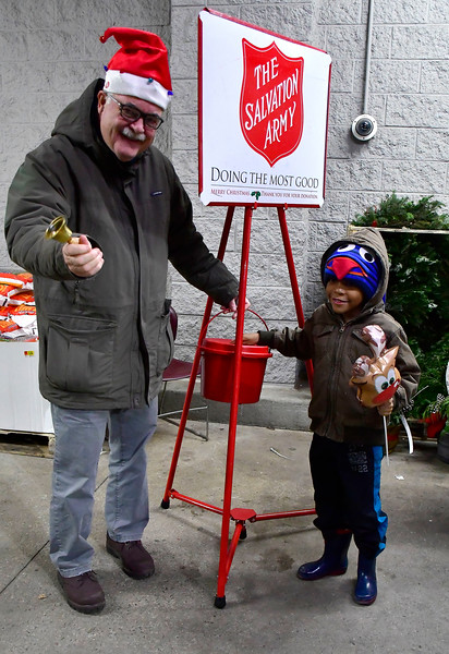 12/19/2018 Mike Orazzi | Staff  State Representative Whit Betts (R-78) accepts a donation from Ayden Miller,6,  while participating in The Salvation Army's Red Kettle Campaign by ringing bells at Walmart on Farmington Avenue in Bristol. Wednesday.