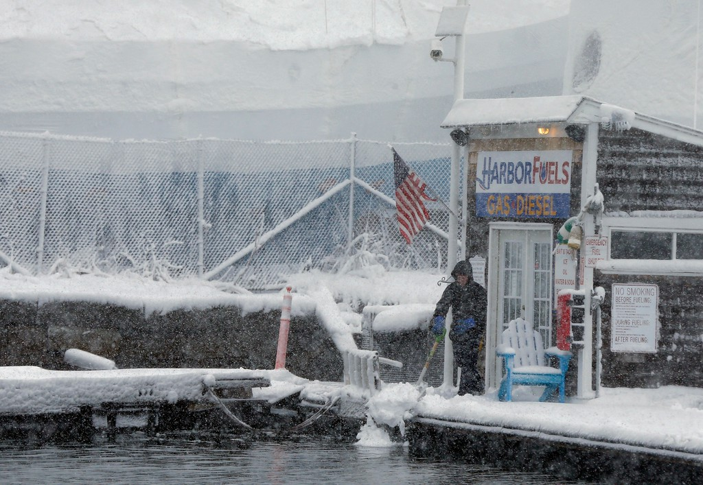 . A worker clears snow from the fuel dock at the Boston Harbor Shipyard and Marina in Boston, Tuesday, March 13, 2018. Boston finds itself in the bullseye of the third nor\'easter in two weeks, with forecasters warning of up to 18 inches of snow and 2 feet or more to the south. (AP Photo/Michael Dwyer)