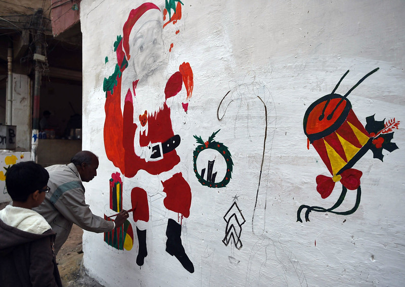 . A Pakistani minority Christian paints a Santa Claus drawing on a wall in a slum area of Karachi on December 24, 2014. Pakistan is overwhelmingly Muslim and at around two percent of the population, Christians are among the country\'s most marginalized citizens. ASIF HASSAN/AFP/Getty Images