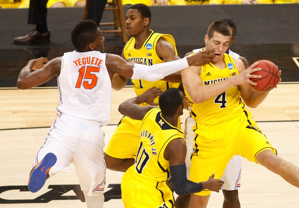 . Michigan Wolverines forward Mitch McGary (R) battles for the ball with Florida Gators forward Will Yeguete in their South Regional NCAA men\'s basketball game in Arlington, Texas March 31, 2013. REUTERS/Tim Sharp